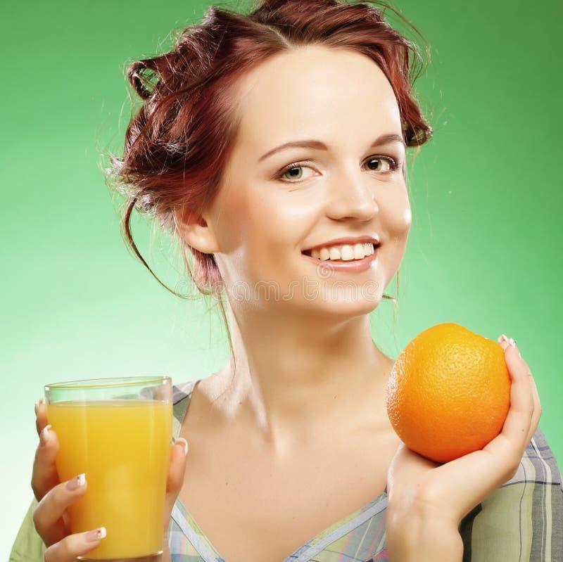 Frau mit Orangensaft über grünem Hintergrund lizenzfreie stockbilder