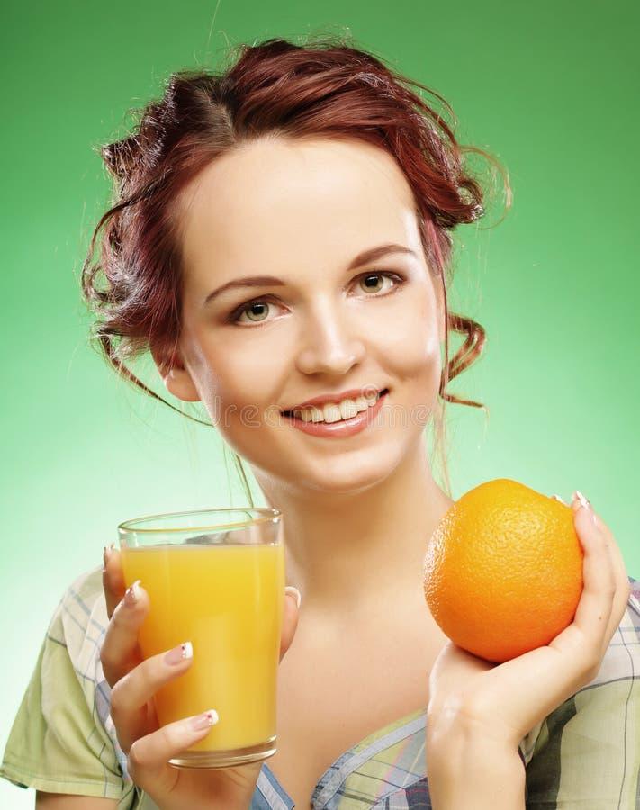 Frau mit Orangensaft über grünem Hintergrund stockbilder