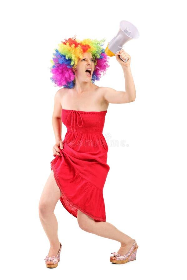 Frau mit Perücke schreiend auf einem Megaphon lizenzfreie stockfotos