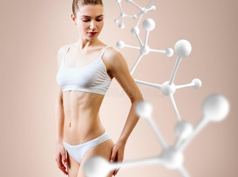 Frau mit perfektem Körper nahe großer Molekülkette Abnehmen des Konzeptes stockfoto