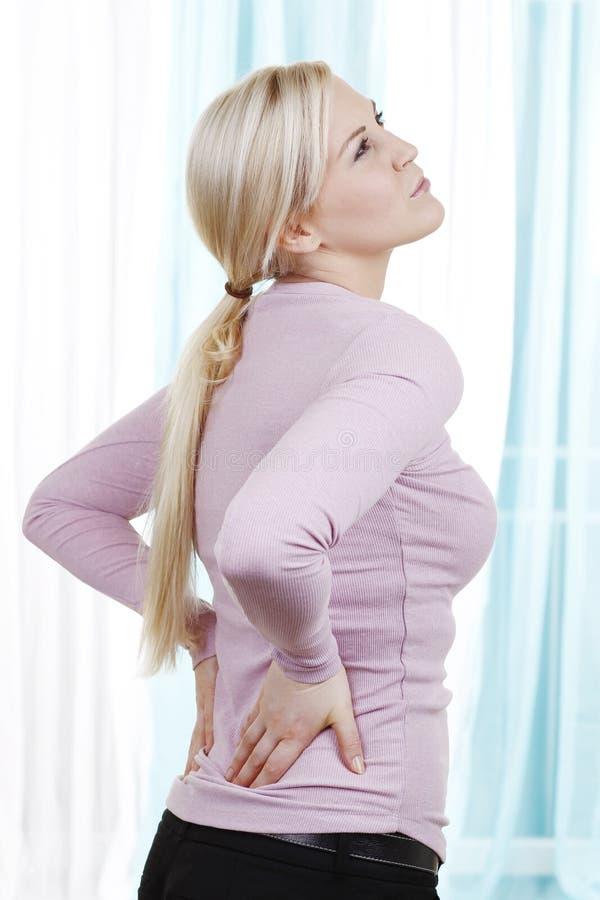 Frau mit Rückenschmerzen stockfotos