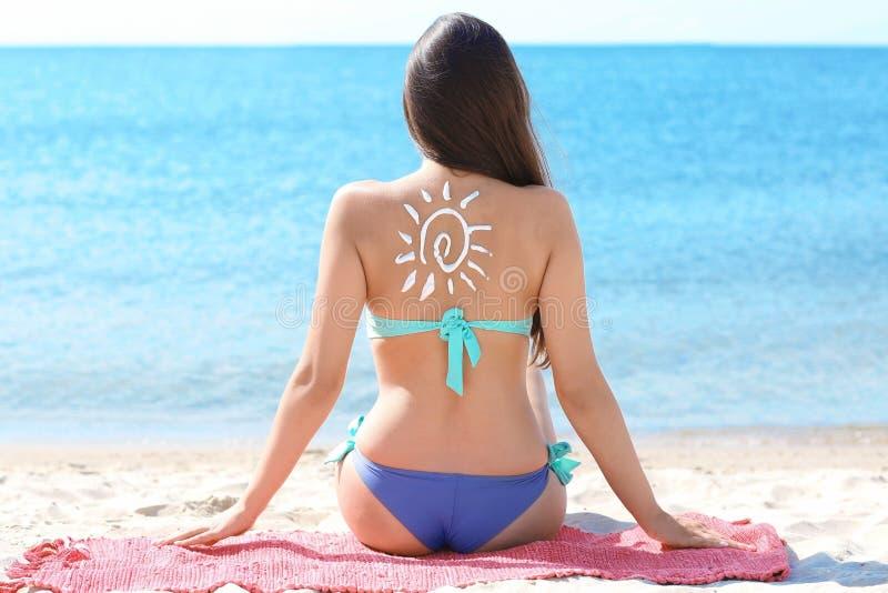 Frau mit Rückseite der Sonnenblock-Creme an lizenzfreie stockfotografie