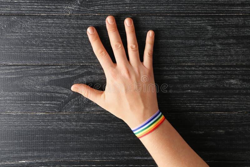 Frau mit Regenbogenarmband von LGBT auf hölzernem Hintergrund stockfotografie