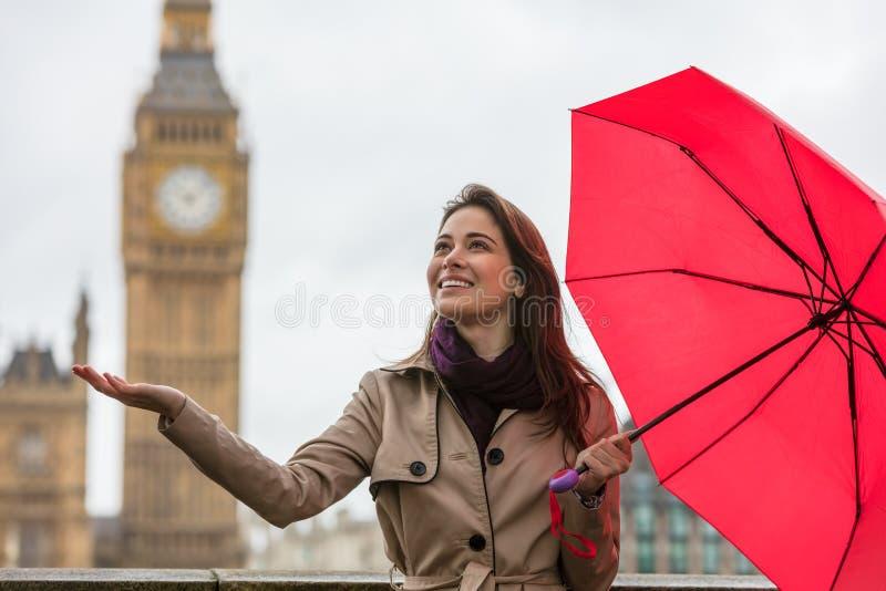 Frau mit Regenschirm durch Big Ben, London, England lizenzfreie stockbilder