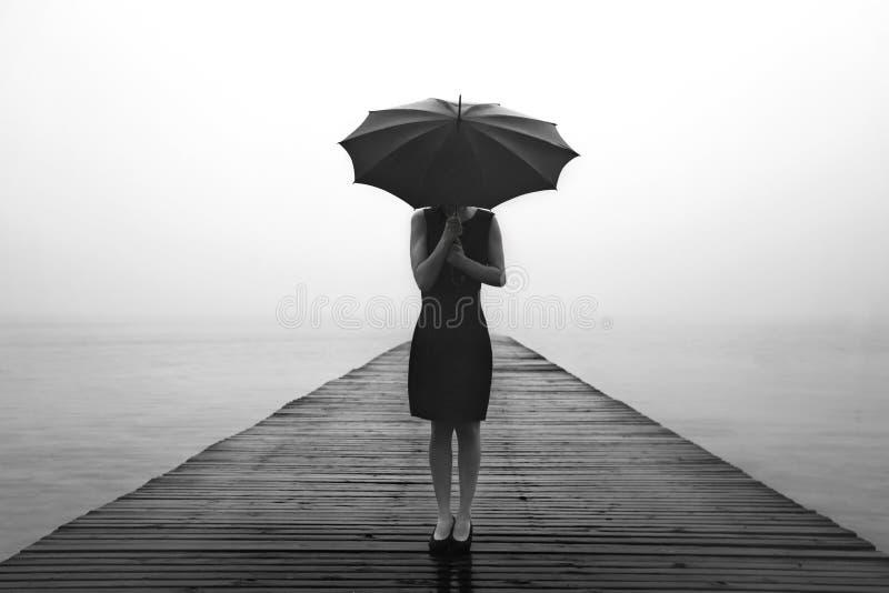 Frau mit Regenschirm erwägt friedlich die Natur lizenzfreie stockfotos