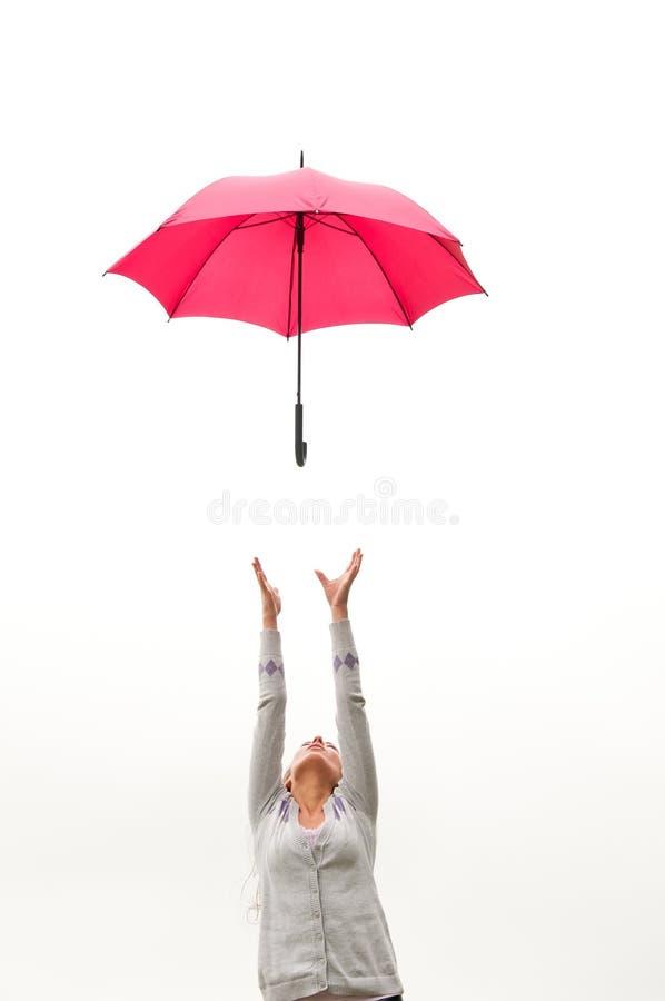 Frau mit Regenschirm im Wind stockfotografie