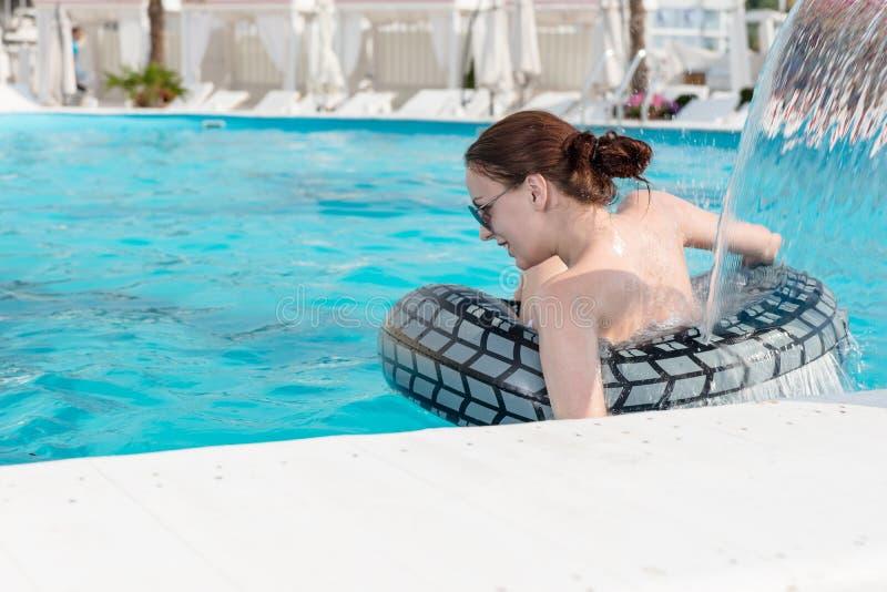 Frau mit Rettungsring unter Swimmingpool-Wasserfall stockfoto