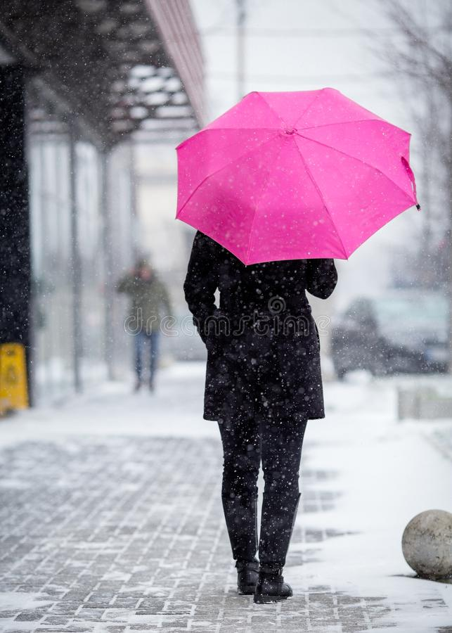 Frau mit rosa Regenschirm am Schneetag stockbild