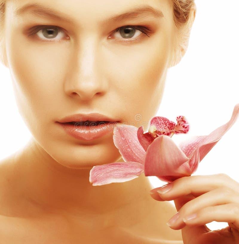 Frau mit rosafarbener Orchidee lizenzfreie stockfotos