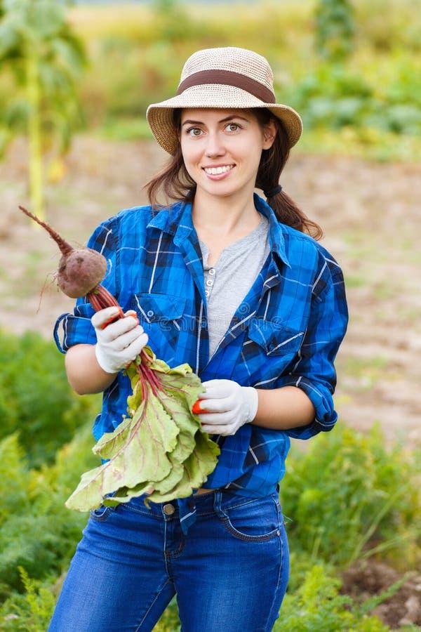 Frau mit Rote-Bete-Wurzeln im Garten lizenzfreie stockfotos