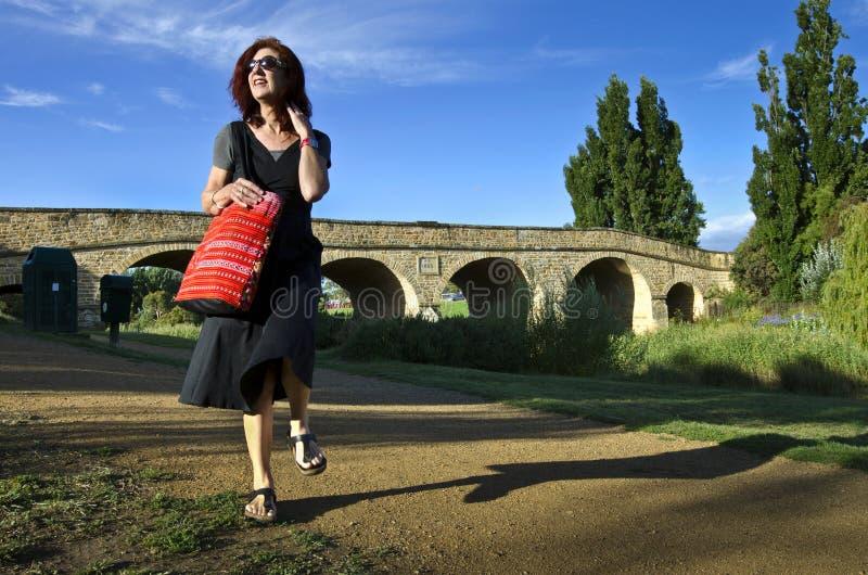 Frau mit rotem Beutel an der Richmond-Brücke, Tasmanien lizenzfreie stockbilder
