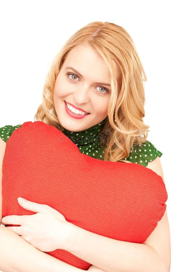 Frau mit rotem heart-shaped Kissen stockbild