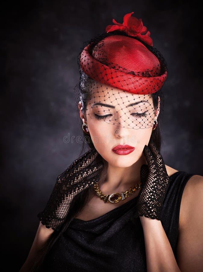 Frau mit rotem Hut und schwarzen Handschuhen stockbild