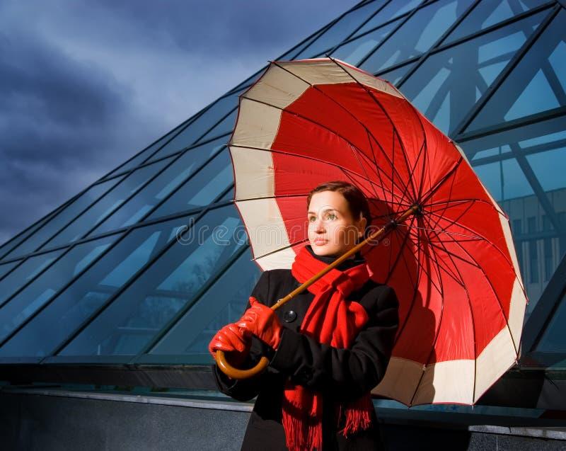 Frau mit rotem Regenschirm lizenzfreie stockbilder