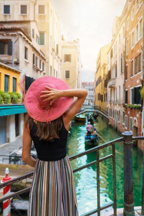 Frau mit rotem sunhat genießt die Ansicht zu einem Kanal in Venedig, Italien stockfotografie