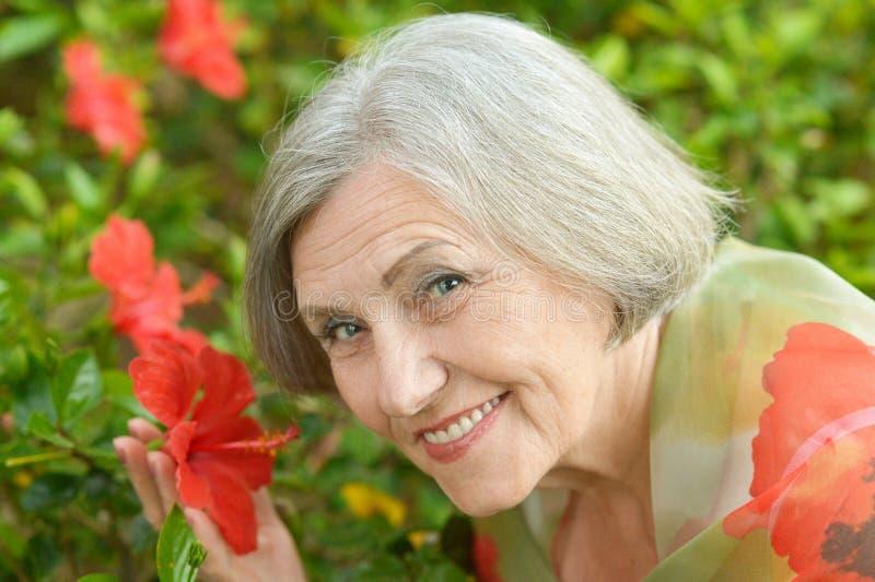 Frau mit roten Blumen lizenzfreie stockfotografie