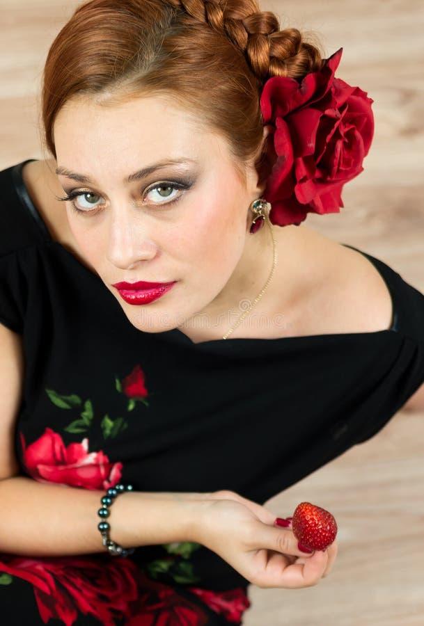 Frau mit roter Blume im schwarzen Kleid mit Erdbeere stockfotos