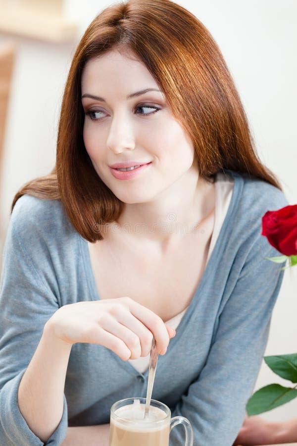 Frau mit Rotrose am Café stockbild