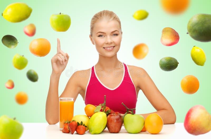 Frau mit Saft und Früchten Finger oben zeigend lizenzfreies stockbild