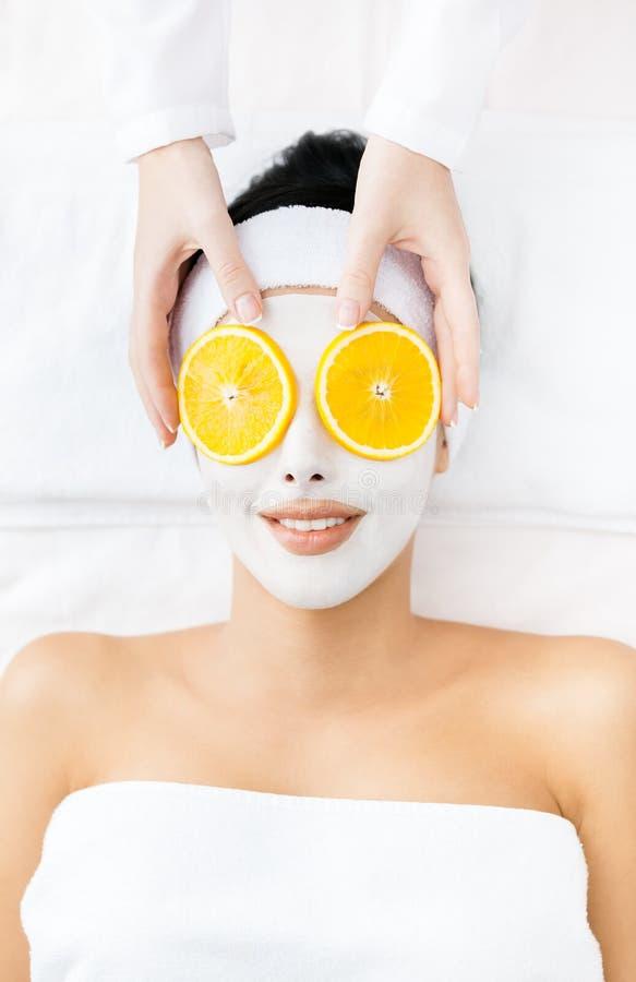 Frau mit Sahne auf Gesichts- und Orangenschnitten auf Augen lizenzfreie stockfotos