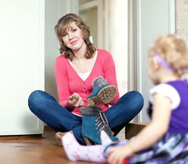 Frau mit Schätzchen säubert Fußbekleidung lizenzfreie stockfotos
