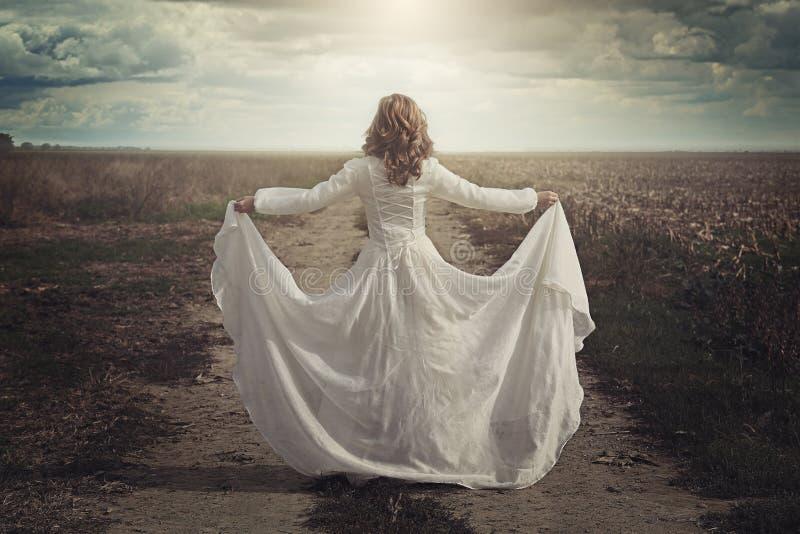 Frau mit schönem Kleid auf den Landgebieten stockbild