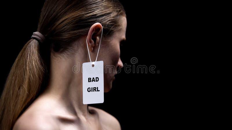 Frau mit schlechtem Mädchenaufkleber auf Ohr gegen schwarzen Hintergrund, Verhaltenstereotypen lizenzfreie stockfotos