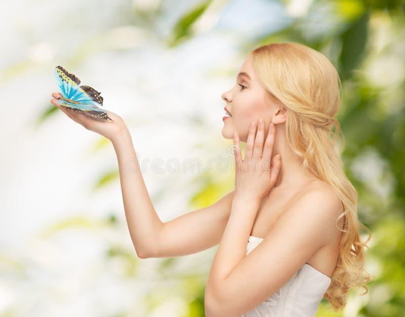 Frau mit Schmetterling in der Hand lizenzfreie stockbilder