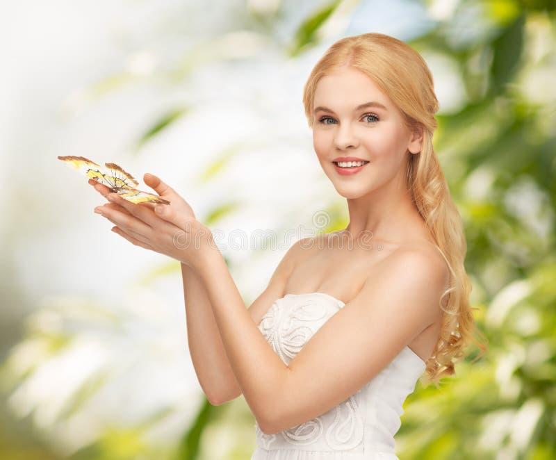 Frau mit Schmetterling in der Hand lizenzfreie stockfotos