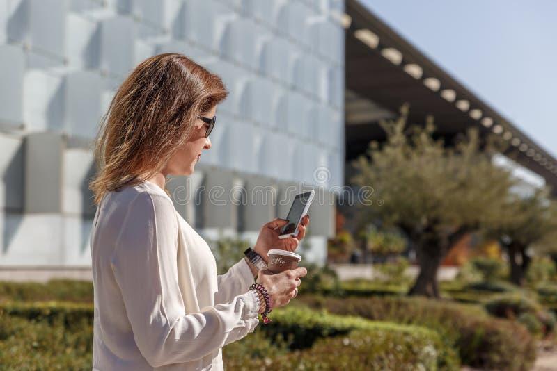 Frau mit schwarzen Gläsern überprüft ihren Handy in der Straße, beim Trinken eines Kaffees lizenzfreie stockfotos