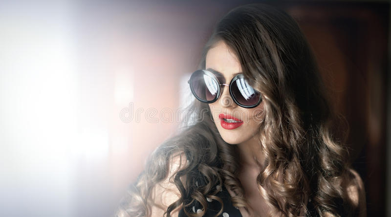 Frau mit schwarzer Sonnenbrille und dem langen gelockten Haar Schönes Frauenportrait Arbeiten Sie Kunstfoto des jungen Modells mi lizenzfreies stockbild