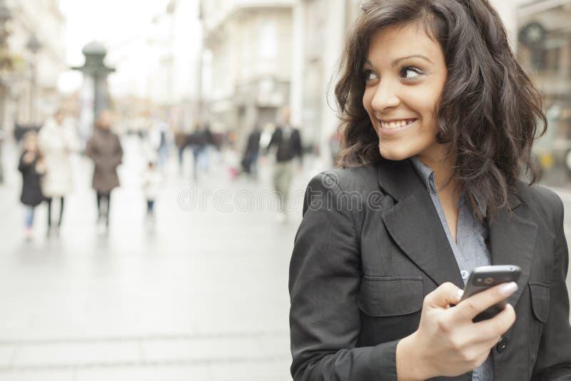 Frau mit smartphone in den Händen gehend auf Straße lizenzfreie stockbilder