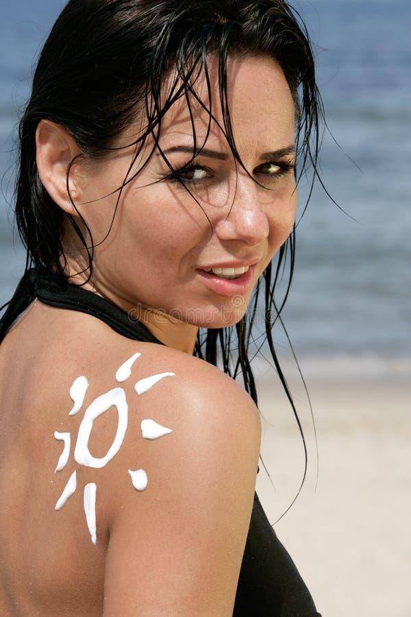 Frau mit Sonne-geformter Sonnesahne lizenzfreies stockfoto