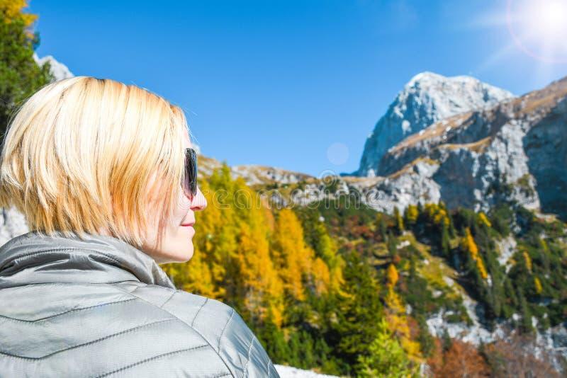 Frau mit Sonnenbrille an einem sonnigen Tag des netten Herbstes auf einer Reise im julianischen Alpentrekkingshoch in den Bergen lizenzfreies stockbild