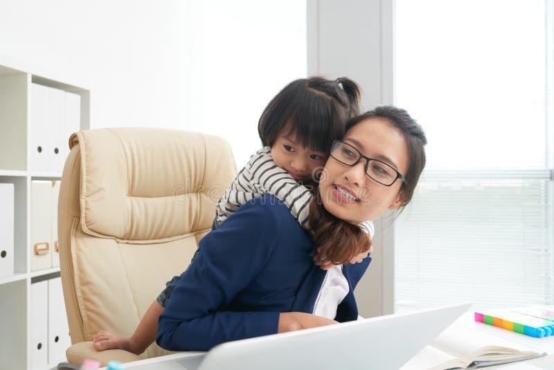 Frau mit spielerischem Mädchen im Büro lizenzfreie stockfotos