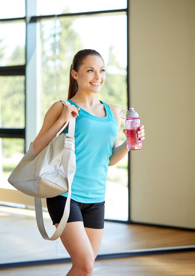 Frau mit Sport bauschen sich und Flasche Wasser in der Turnhalle stockfotografie