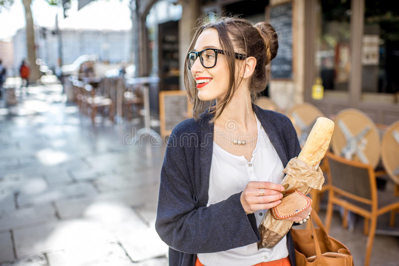 Frau mit Stangenbrot in der Stadt stockfotos