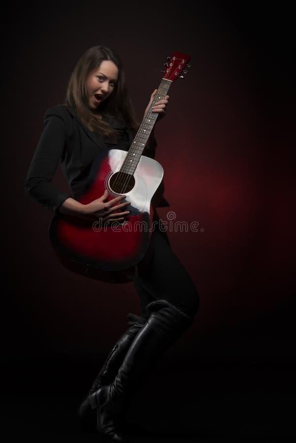 Ausdrucksvolle Frau, die Gitarre spielt stockbilder