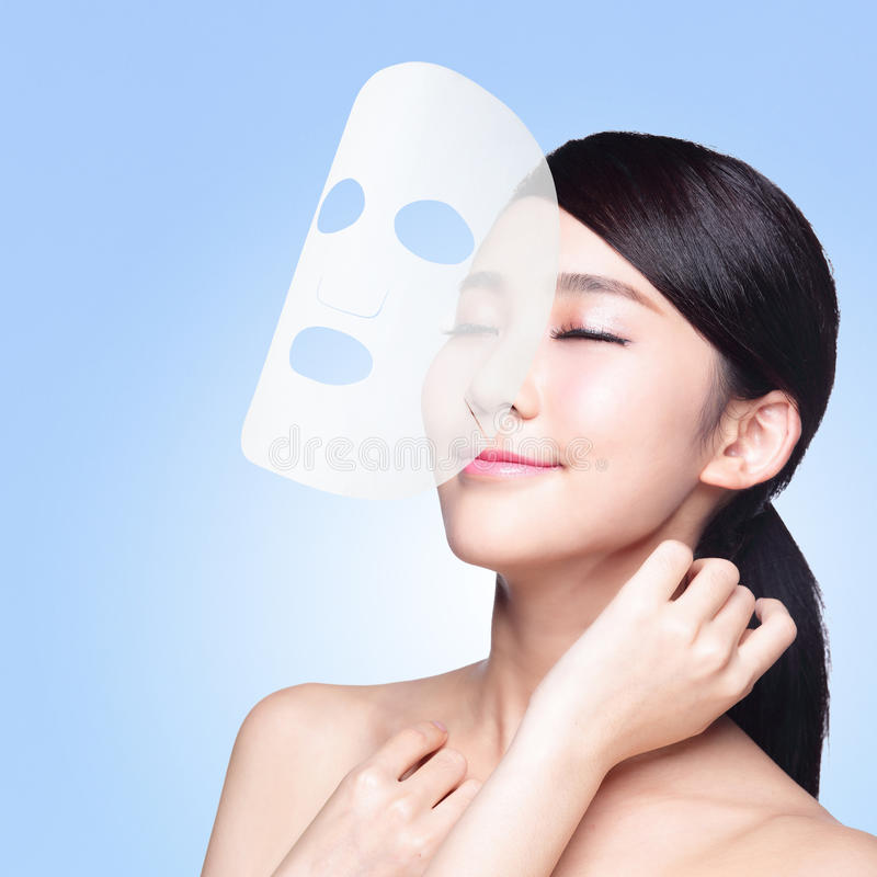 Frau mit Stoffgesichtsbehandlungsmaske stockbild