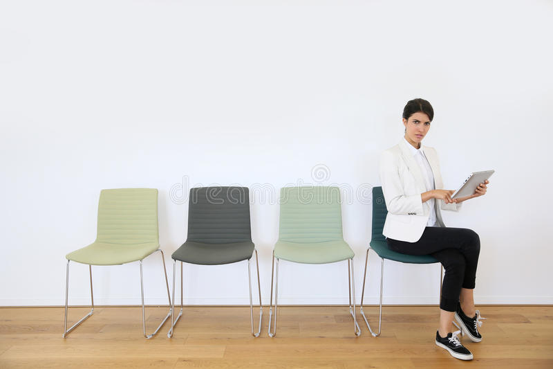 Frau mit Tablette im Warteraum stockfoto