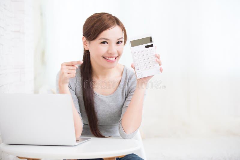 Frau mit Taschenrechner und Laptop stockfoto