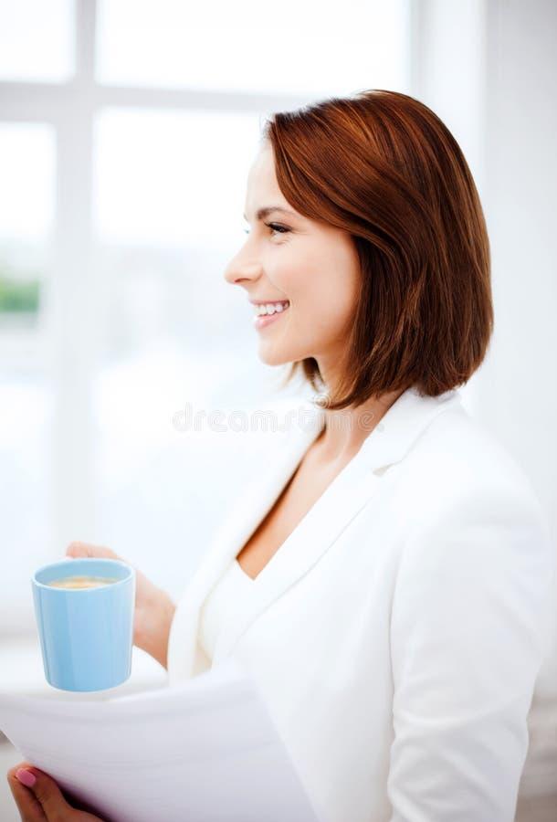 Frau mit Tasse Kaffee und Papieren stockbilder