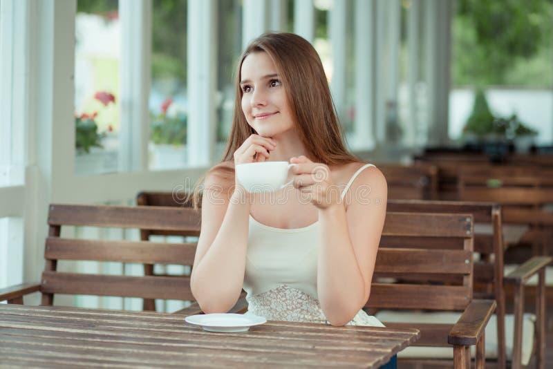 Frau mit Tasse Tee, die auf der Terrasse eines Coffeeshops nachdenklich aussieht lizenzfreie stockbilder