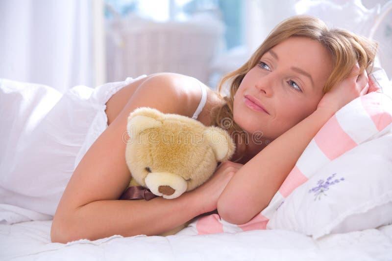 Frau mit Teddybären im Bett stockfotos