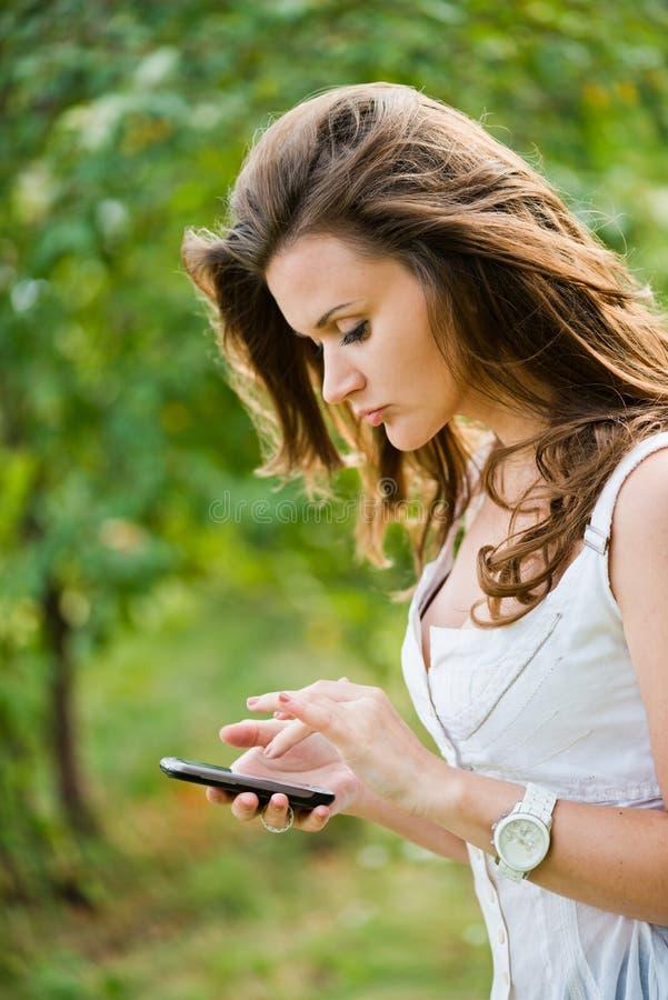 Frau mit Telefon. Texting stockbild