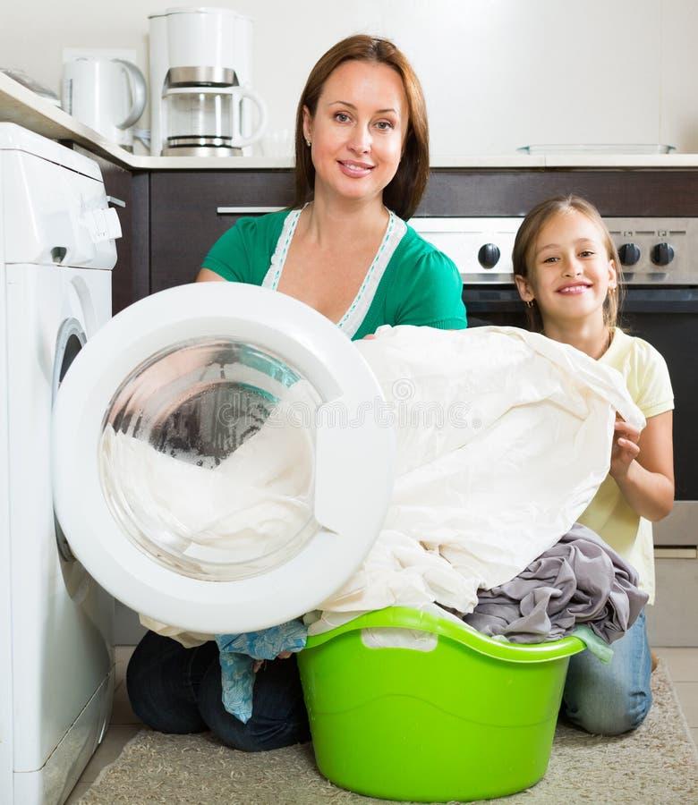 Frau mit Tochter nahe Waschmaschine lizenzfreie stockfotografie