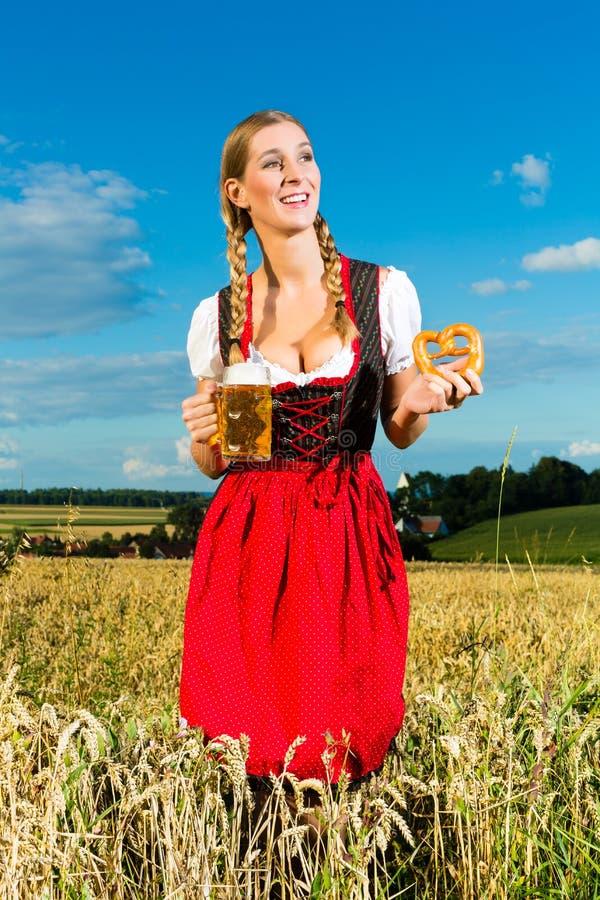 Frau mit tracht, Bier und Brezel im Bayern stockbild