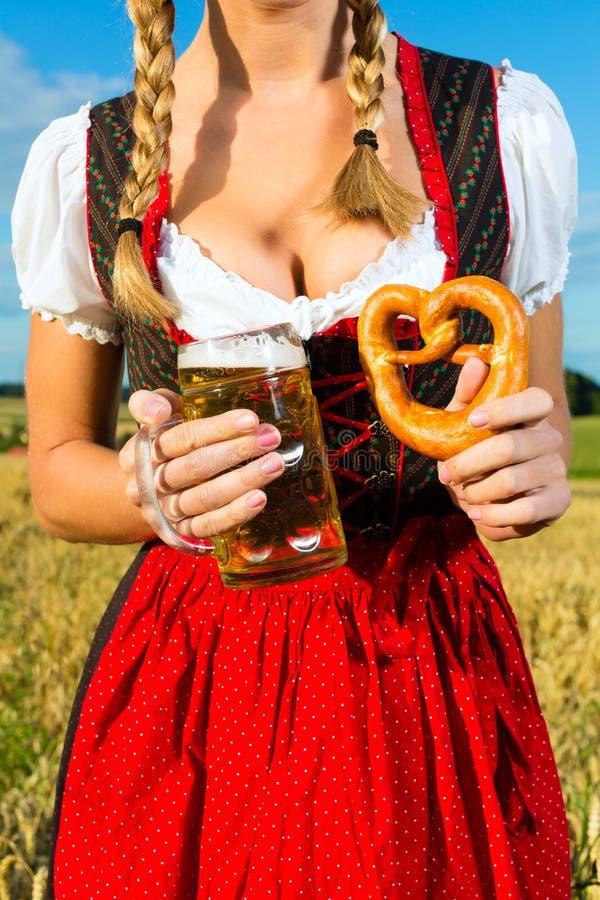 Frau mit tracht, Bier und Brezel im Bayern stockfotografie