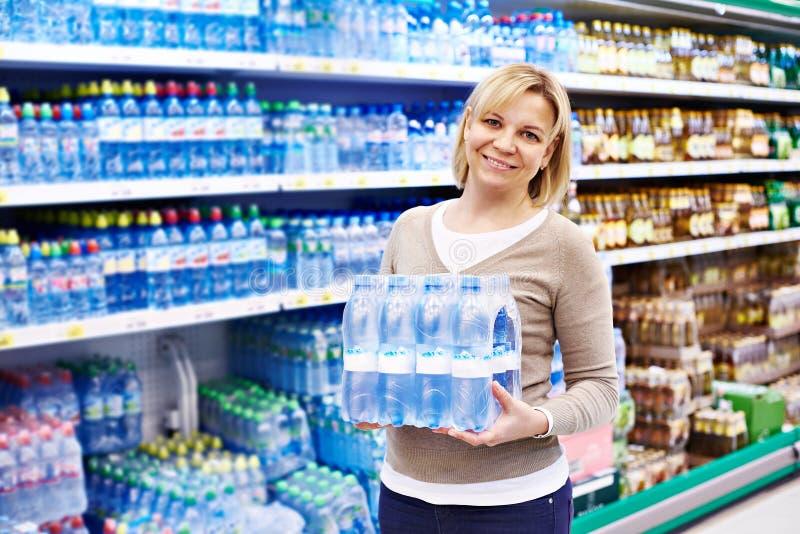 Frau mit Trinkwasser der Verpackung lizenzfreies stockbild