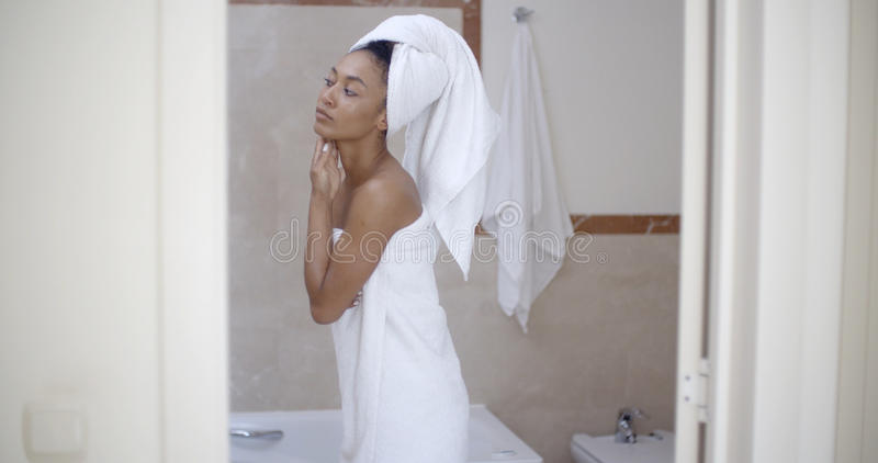 Frau mit Tuch auf Kopf im Badezimmer stockfotos